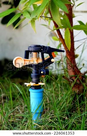 Sprinkler for watering garden on a green grass - stock photo