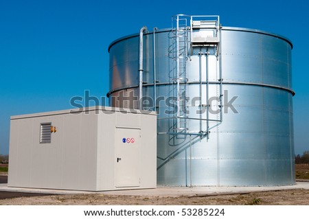 sprinkler water tank with pump building - stock photo
