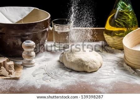 Sprinkling flour pizza dough - stock photo
