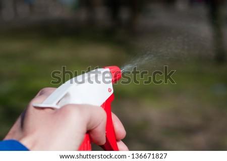 sprinkling water sprayer in hand - stock photo