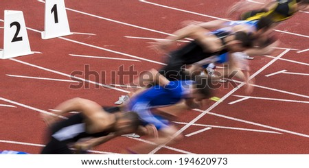 sprint start in track and field in blured motion - stock photo