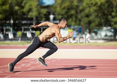 Sprinter leaving  on the running track. Explosive start. - stock photo
