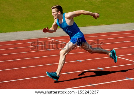 Sprinter leaving starting blocks on running track - stock photo