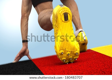 Sprinter starts on banner with german national colors - stock photo