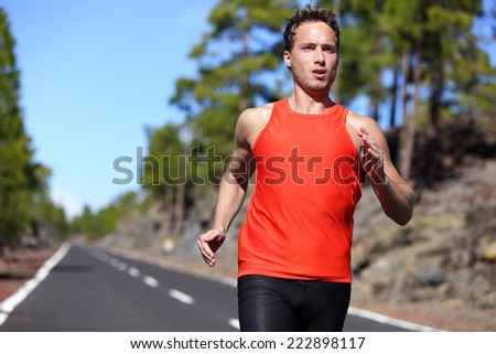 Sprinting runner man running at fast speed. Male sport sprinter training hard. Young strong male fitness model during run outdoors in beautiful landscape. - stock photo