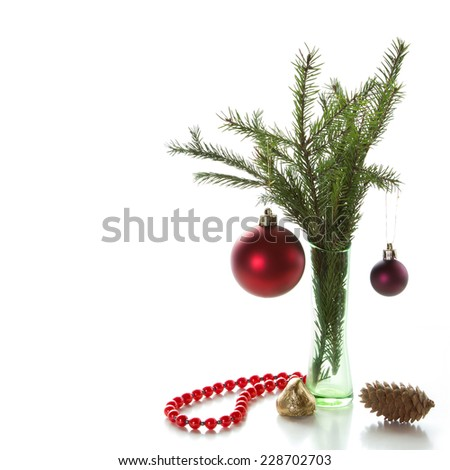 Spruce branches with cones and Christmas decorations on a white background. Space for text. - stock photo