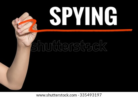 Spying word write on black background by woman hand holding highlighter pen - stock photo