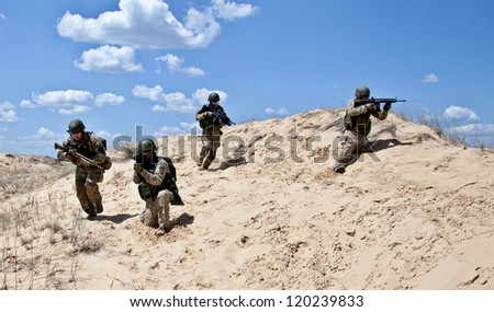 Squad of soldiers run through the desert through the military operation - stock photo