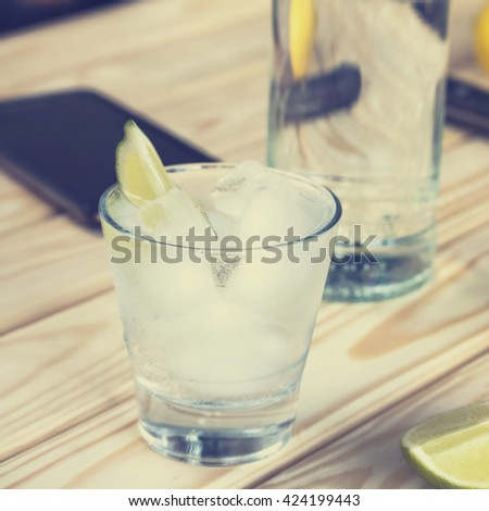 square frame. Cocktail vodka or gin with ice vintage. Closeup.  Selective focus, blur, background, vodka in a glass with ice, lime, a cocktail bar, alcohol, alcoholic beverage.  - stock photo