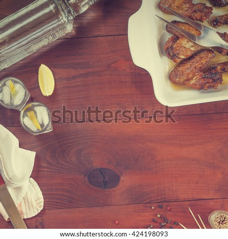 square frame. Vodka, gin, tequila in a glass with ice, fried chicken legs and fried chicken wings , Cherry tomatoes, Spices, Italian food . top view, closeup  - stock photo