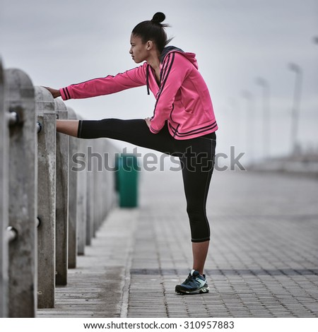 Square image of a young athlete busy stretching on the railing of the paved walkway along the ocean side - stock photo