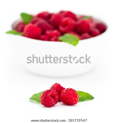 Square image of three red raspberries with fresh mint leaves in front of white bowl with raspberries - isolated on white background - stock photo