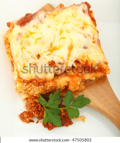 Square of baked lasagna with parsley on bamboo serving spoon - stock photo