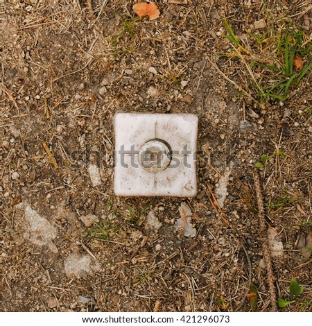 Square photo of border marker. Plastic border marker separating land plots. Plastic cube in soil. Marker placed in the earth. Dividing mark of land. Boarder between land plots. - stock photo