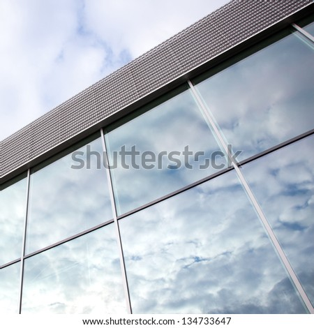square picture of clouds reflected in windows of office building - stock photo