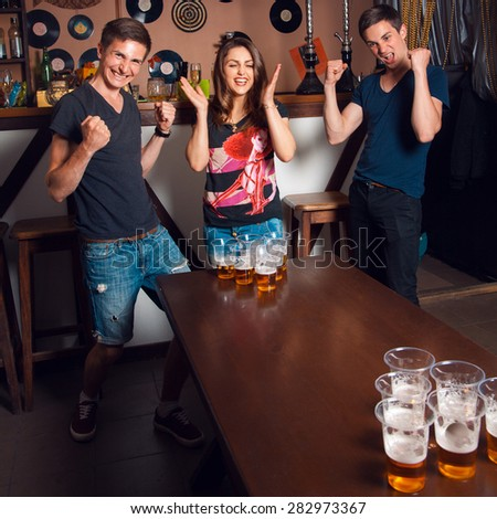 Square picture of sweet adult woman and twins playing beerpong at bar.  - stock photo
