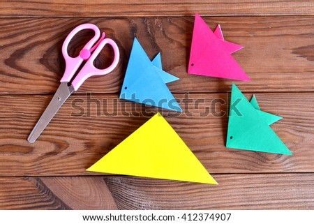 Square piece of origami paper folded diagonally. Set of colorful origami fish, scissors on a wooden table. Kids crafts  - stock photo