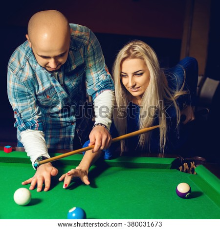 Square portrait of beautiful couple plays billiard on the pool table. Billiard sport concept. American pool billiard. Pool billiard game. - stock photo