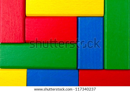 Square shape colorful background in red, yellow, green, and blue created of wooden toy blocks - stock photo