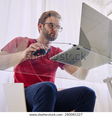 Square shot of a young professional business man busy studying on his glass desk shot from under the table through the glass, as he works on his silver notebook in his red shirt with a beard - stock photo
