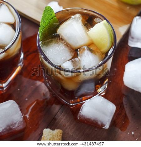 Square shot. rum cocktail in a glass with ice, lime, mint, bread on a wooden table, brandy - stock photo