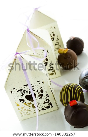 Square white decorative lace heart favor boxes filled with gourmet truffles. - stock photo