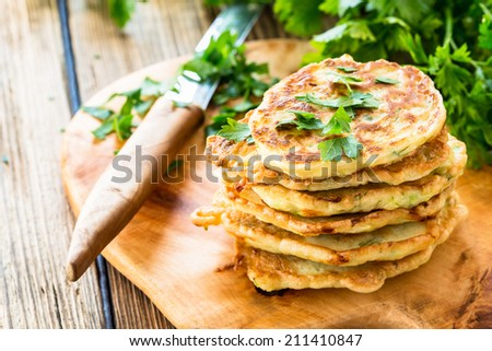 Squash and  zucchini fritters on wooden table - stock photo