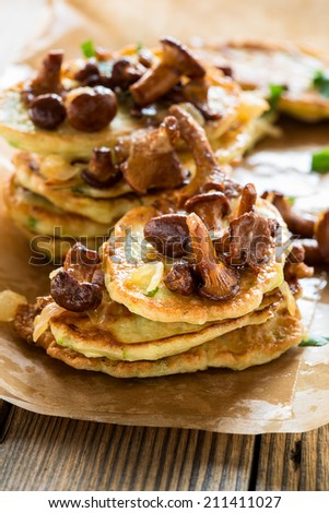 Squash and  zucchini fritters with chanterelle mushrooms on wooden table - stock photo