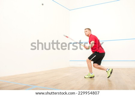 squash player hiting ball in squash court. man playing match of squash alone - stock photo