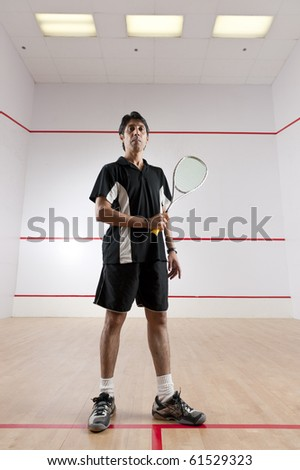 Squash player standing at the T line in a squash court. - stock photo