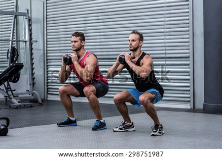 Squatting muscular men exercising with kettlebells - stock photo