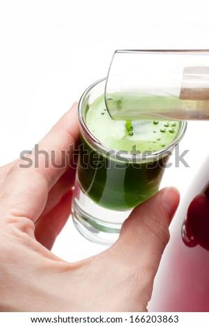 Squeezing wheat grass juice - stock photo