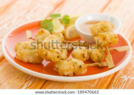 Squid Tempura Skewers - Battered and deep fried calamari on skewers. Served with mango dip. - stock photo