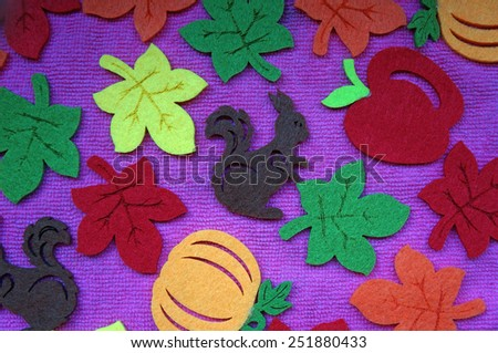 Squirrel and leaves out of felt on a pink fabric as a background                                - stock photo