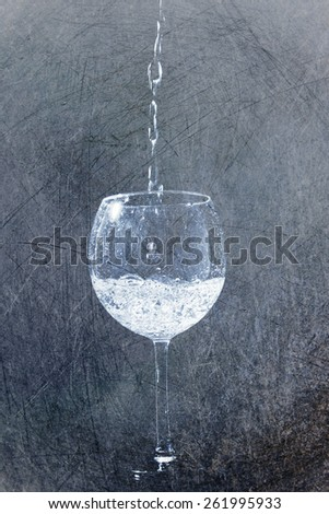 Squirt in glass in drops of water in grunge retro style - stock photo
