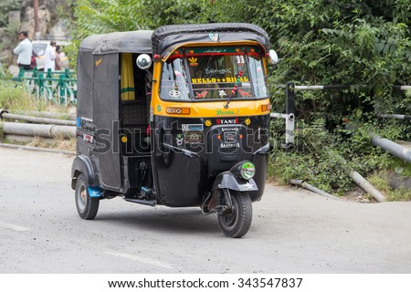 SRINAGAR, INDIA - JULE 02, 2015: Auto rickshaw taxis on a road in Kashmir, India. These iconic taxis have recently been fitted with CNG powered engines in an effort to reduce pollution - stock photo