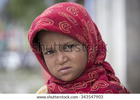 SRINAGAR, INDIA - JUNE 10, 2015: Unidentified beggar girl begs for money from a passerby in Srinagar, Kashmir. Poverty is a major issue in India - stock photo