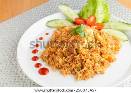 Sriracha shrimp fried rice dish with garnish dots of siracha sauce. - stock photo