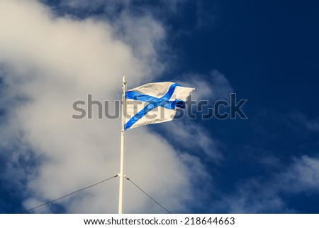 St Andrew's flag on the flagpole waving in the wind against a blue sky - stock photo