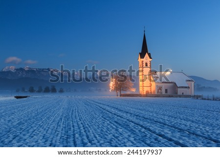 St. Florian church with a view to the alps at dawn on a field near Menges, Slovenia - stock photo