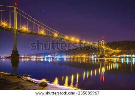 St John's Bridge in Portland, Oregon at night. Glowing lights of the cityscape reflect on the water. This destination is a must see in the pacific northwest. - stock photo