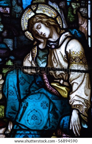St John sleeping under the cross A Victorian stained glass window showing Saint John sleeping under the cross where Jesus Christ is being crucified. - stock photo