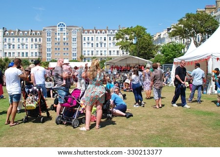 ST.LEONARDS-ON-SEA, ENGLAND - JULY 11, 2015: People enjoy the annual St.Leonards Festival held in Warrior Square Gardens. The free community music and entertainment event was first held in 2006. - stock photo