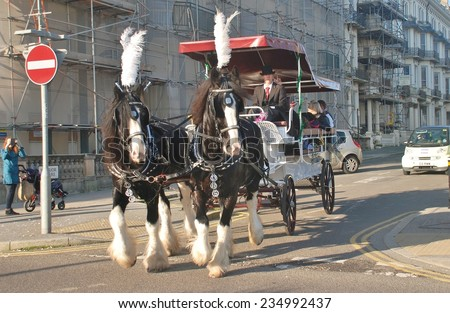 ST.LEONARDS-ON-SEA, ENGLAND - NOVEMBER 29, 2014: Horses pull a carriage giving rides around Warrior Square at the St.Leonards Frost Fair. The event promotes local trade in the approach to Christmas. - stock photo