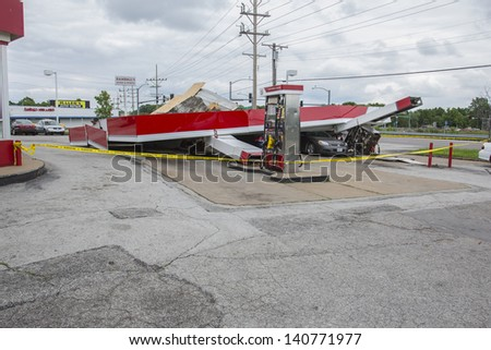 ST. LOUIS - MAY 31, 2013: Cars and homes were heavily damaged by a tornado that swept through Florissant Missouri in the suburbs of St. Louis on, May 31, 2013.This gas station had roof fall on cars. - stock photo