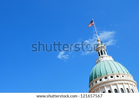 St. Louis Missouri Capitol with American flag against a sky. - stock photo