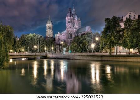 St Luke's Church in Munch at night, alongside the River Isar. - stock photo