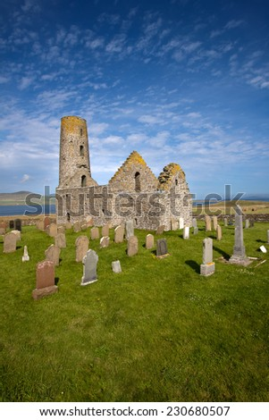 St Magnus Church on the Island of Egilsay, Orkney, Scotland is a partially ruined 12th century Norse structure with a unique round bell tower built near the spot where St Magnus was martyred in 1116. - stock photo