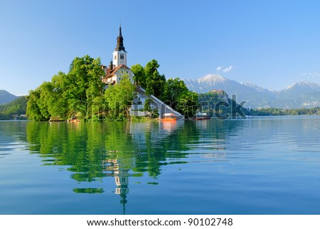 St Martin church on island and Bled lake landscape with mountain - stock photo