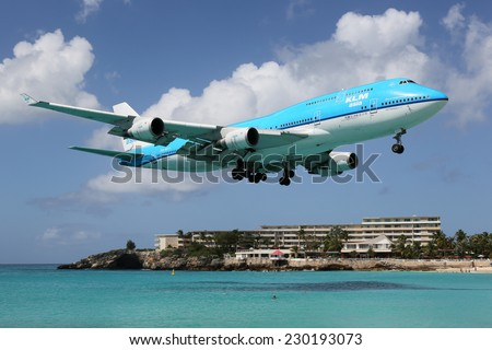 ST. MARTIN, NETHERLANDS ANTILLES - FEBRUARY 9: A KLM Boeing 747 approaching on February 9, 2014 in St. Martin. St. Martin is rated one of the most dangerous airports in the world. - stock photo